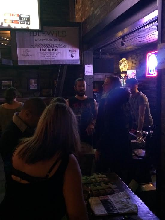 Attendees chat and peruse the night's materials beneath the banner of Idlewild.